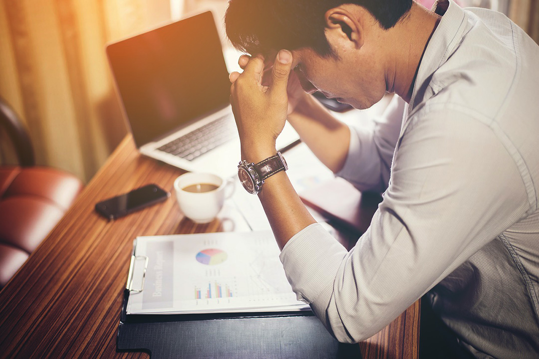 Man stressed looking at paper and laptop