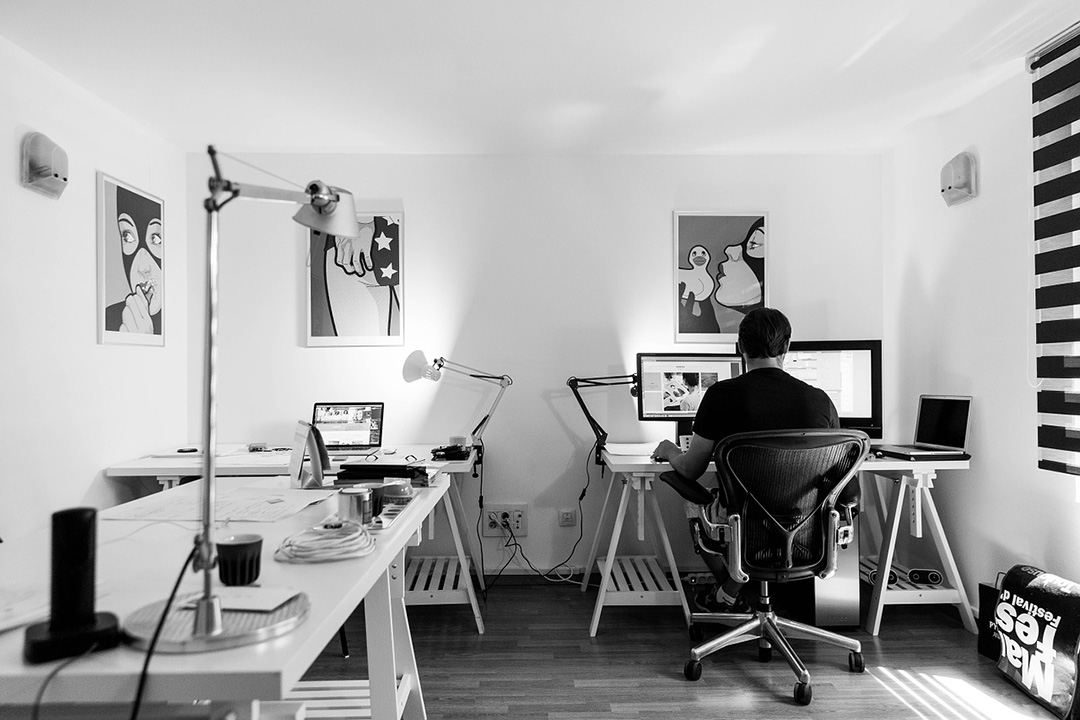 Designer sitting at desk in room with instincts