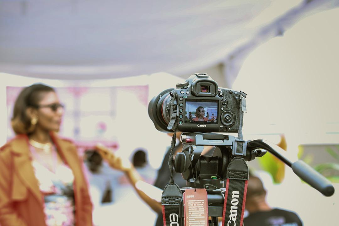 Video DSLR camera on tripod filming woman