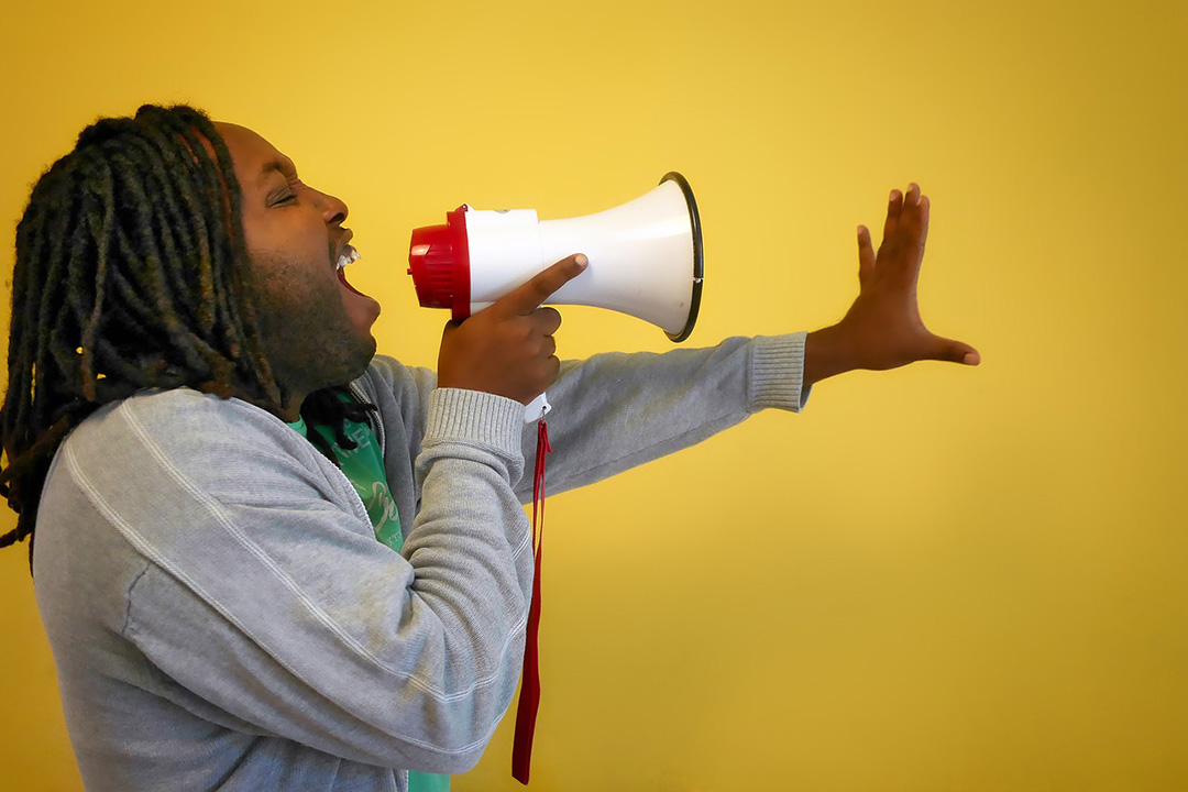 Happy man shouting into megaphone yellow background