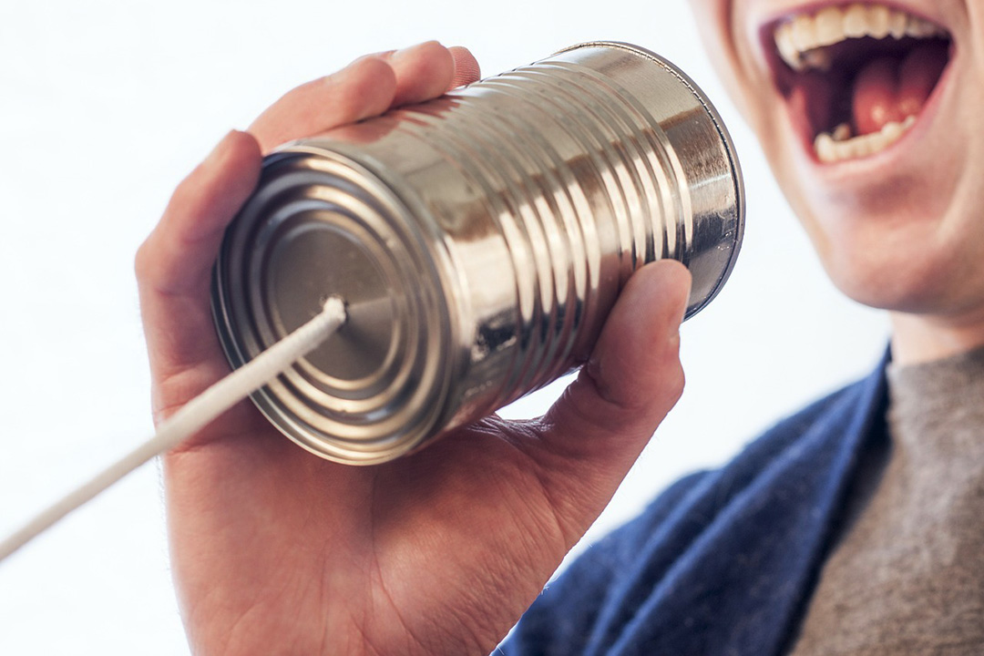 Man speaking word-of-mouth into tin can with string